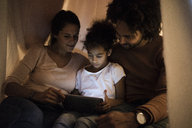 Parents sitting in children's room with daughter, looking at digital tablet - MOEF00301