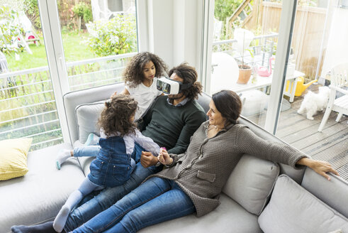 Happy family sitting on couch, father wearing VR goggles - MOEF00304
