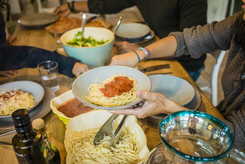 Family sitting at table with spaghetti and tomato sauce - MOEF00334
