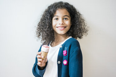 Cheeky little girl smiling at camera, eating ice cream - MOEF00343