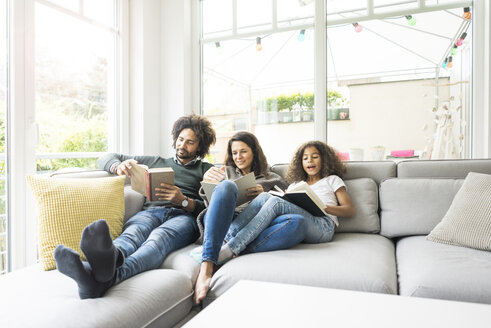 Happy family sitting on couch, reading books - MOEF00352