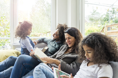 Happy family sitting on couch, reading books - MOEF00355