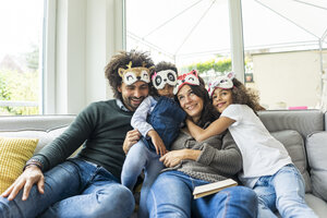 Happy family sitting on couch, wearing animal masks - MOEF00358
