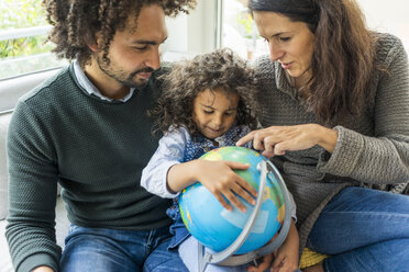 Happy family sitting on couch with globe, daughter learning geography - MOEF00364