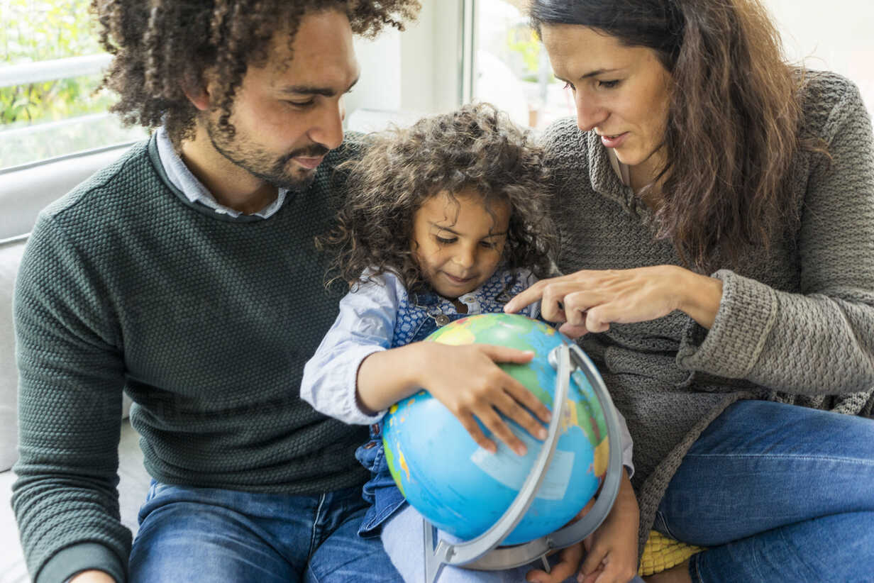 Happy family sitting on couch with globe, daughter learning geography - MOEF00364 - Robijn Page/Westend61