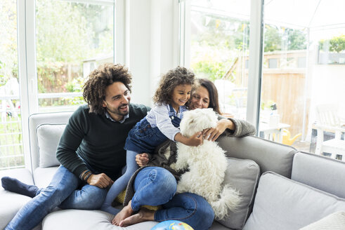 Happy family with dog sitting together in cozy living room - MOEF00367