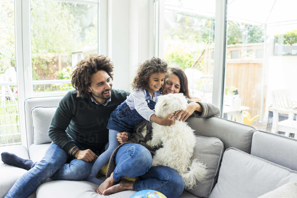 Happy family with dog sitting together in cozy living room - MOEF00367 - Robijn Page/Westend61