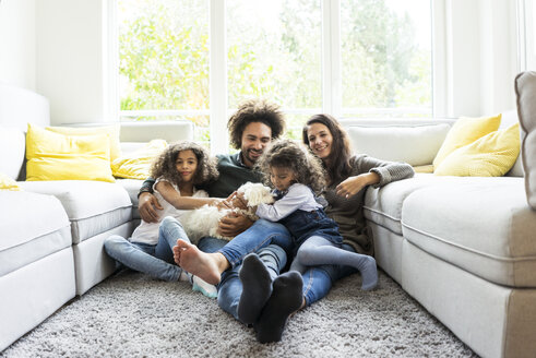 Happy family with dog sitting together in cozy living room - MOEF00370