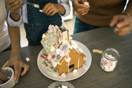 Family pasting gingerbread house in kitchen for Christmas with sweets - MOEF00379