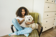 Animal loving little girl sitting in armchair petting her white dog - MOEF00382