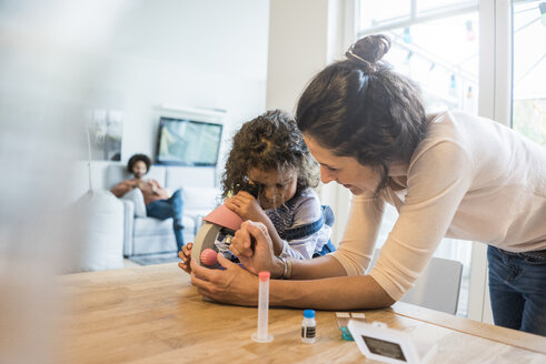 Mother helping daughter with homework, using microscope - MOEF00385