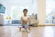 Little girl sitting on skateboard, looking proud - MOEF00400