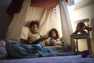 Two sisters sitting in dark children's room, reading a book - MOEF00403