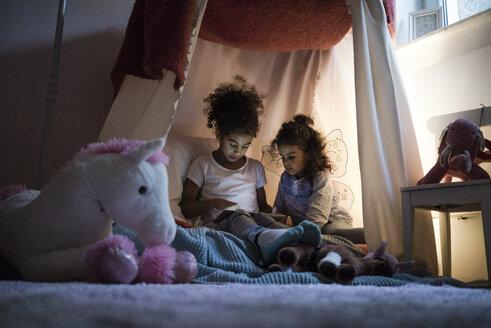 Two sisters sitting in dark children's room, looking at digital tablet - MOEF00409