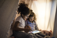 Two sisters sitting in dark children's room, looking at digital tablet - MOEF00412