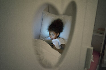 Little girl sitting in dark children's room, looking at digital tablet - MOEF00415