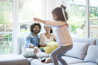 Parents sitting on couch, while daughter is jumping and having fun - MOEF00421