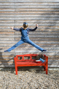 Girl jumping in the air in front of a wooden facade - OJF00208