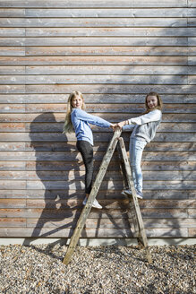 Two girls standing on a ladder in front of a wooden facade - OJF00211