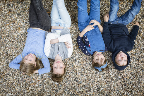 Three girls and a boy lying on the ground covered with pebbles - OJF00220