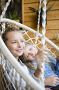 Two happy girls relaxing together in a hanging chair - OJF00223