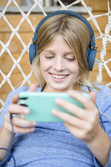 Portrait of happy girl with headphones and smartphone in a hanging chair - OJF00226