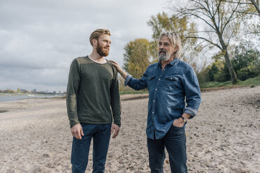 Father and son taking a stroll at Rhine river, meeting to talk - KNSF02873