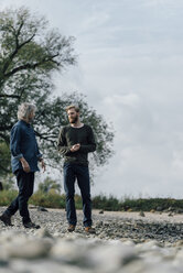 Father and son meeting at Rhine river in autmn, talking together - KNSF02930