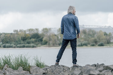 Senior man standing on stones looking at Rhine river - KNSF02939
