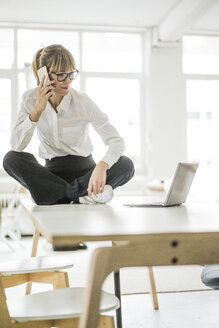 Businesswoman sitting on desk in office with laptop and cell phone - JOSF01945