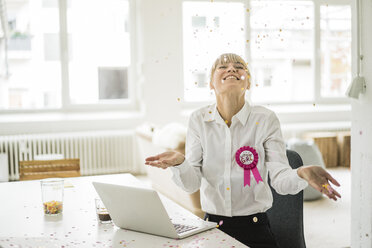 Confetti falling on businesswoman celebrating birthday in office - JOSF01960