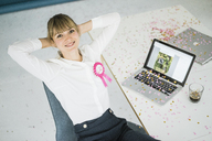 Portrait of smiling businesswoman with laptop in office celebrating her birthday - JOSF01966