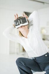Businesswoman wearing VR glasses pretending to be a bunny - JOSF01975