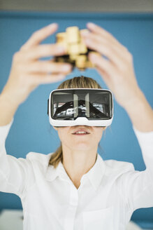 Businesswoman wearing VR glasses holding cubical structure - JOSF01978