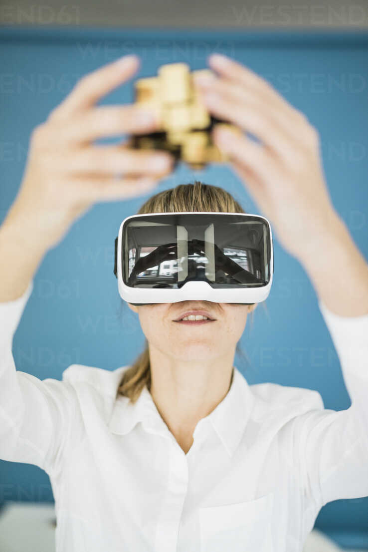Businesswoman wearing VR glasses holding cubical structure - JOSF01978 - Joseffson/Westend61