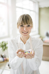Portrait of smiling woman holding buttons - JOSF01990