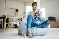 Smiling woman sitting in beanbag using cell phone - JOSF02002