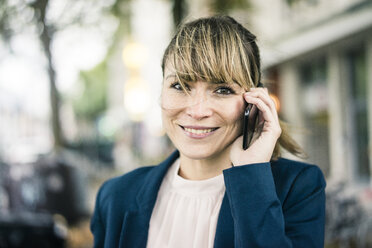 Portrait of smiling businesswoman on cell phone outdoors - JOSF02011