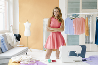 Portrait of smiling young woman in fashion studio - KNSF02970