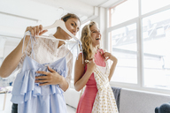 Two happy young women holding dresses - KNSF02985