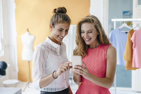 Two smiling young women with cell phone in fashion studio - KNSF02988