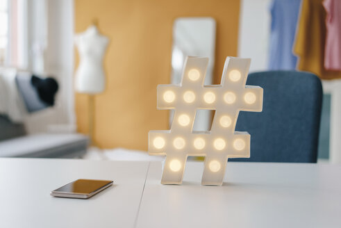Illuminated hashtag sign on table in fashion studio - KNSF02991