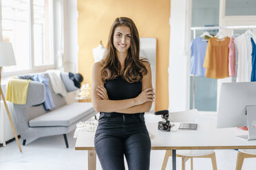 Portrait of smiling young woman in fashion studio with camera on table - KNSF02994