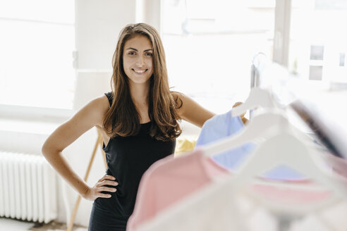 Portrait of smiling young woman in fashion studio - KNSF03000