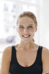 Portrait of smiling young woman in sportswear - KNSF03015