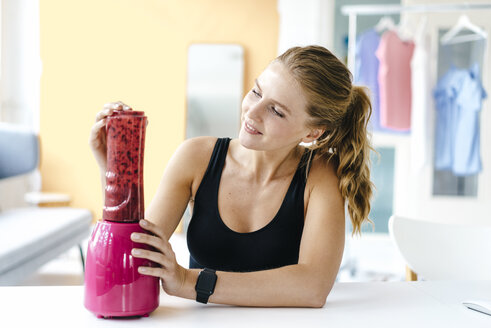 Smiling young woman in sportswear preparing a smoothie - KNSF03024