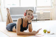 Smiling young woman in sportswear lying on gym mat listening to music - KNSF03027