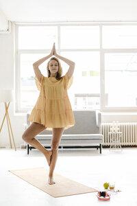 Young woman wearing a dress practising yoga - KNSF03030