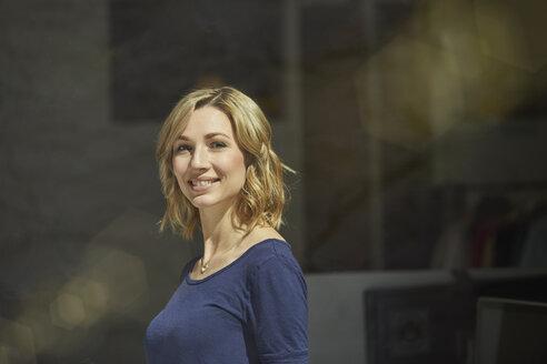 Portrait of blond woman behind window pane, smiling - PNEF00350