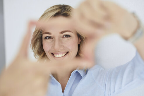 Portrait of smiling blond woman building frame with her fingers while looking at viewer - PNEF00362